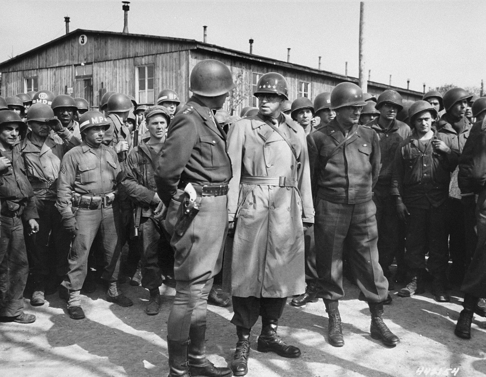 General George S. Patton (with his back to camera) converses with General Omar Bradley during their tour of the newly liberated Ohrdruf concentration camp.