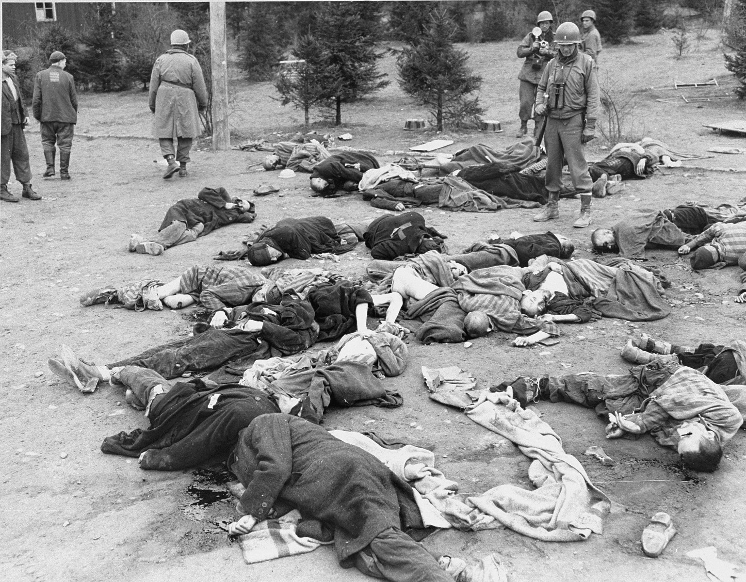 American soldiers view the bodies of prisoners that lie strewn on the ground in the newly liberated Ohrdruf concentration camp.  1st Lieutenant Earl J. Kelly is standing on the right.