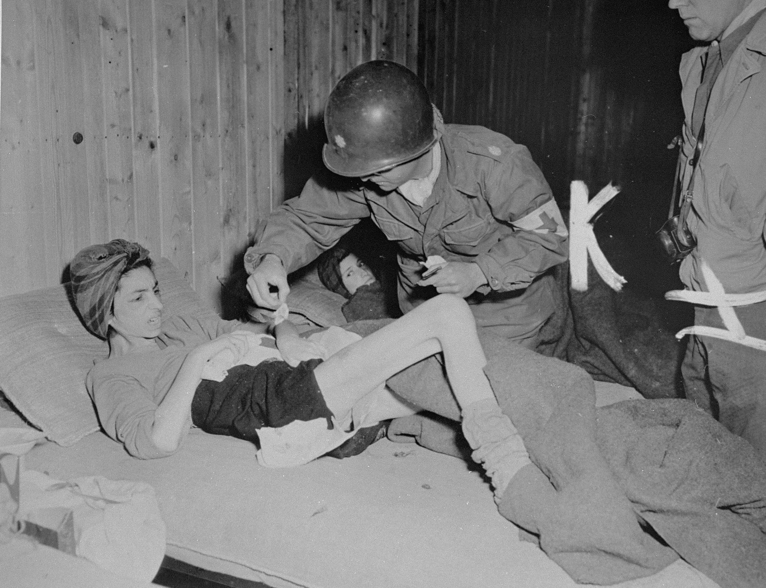 Lt. Col. J.W. Branch, Chief Surgeon of the 6th Armored Division, 3rd U.S. Army, dresses body sores of a Hungarian woman survivor in Penig, a sub-camp of Buchenwald.    SS guards evacuated all those prisoners who could still walk upon the approach of American troops, leaving behind those too ill to move.  Women in the camp suffered from starvation, typhus, diptheria, and tuberculosis.