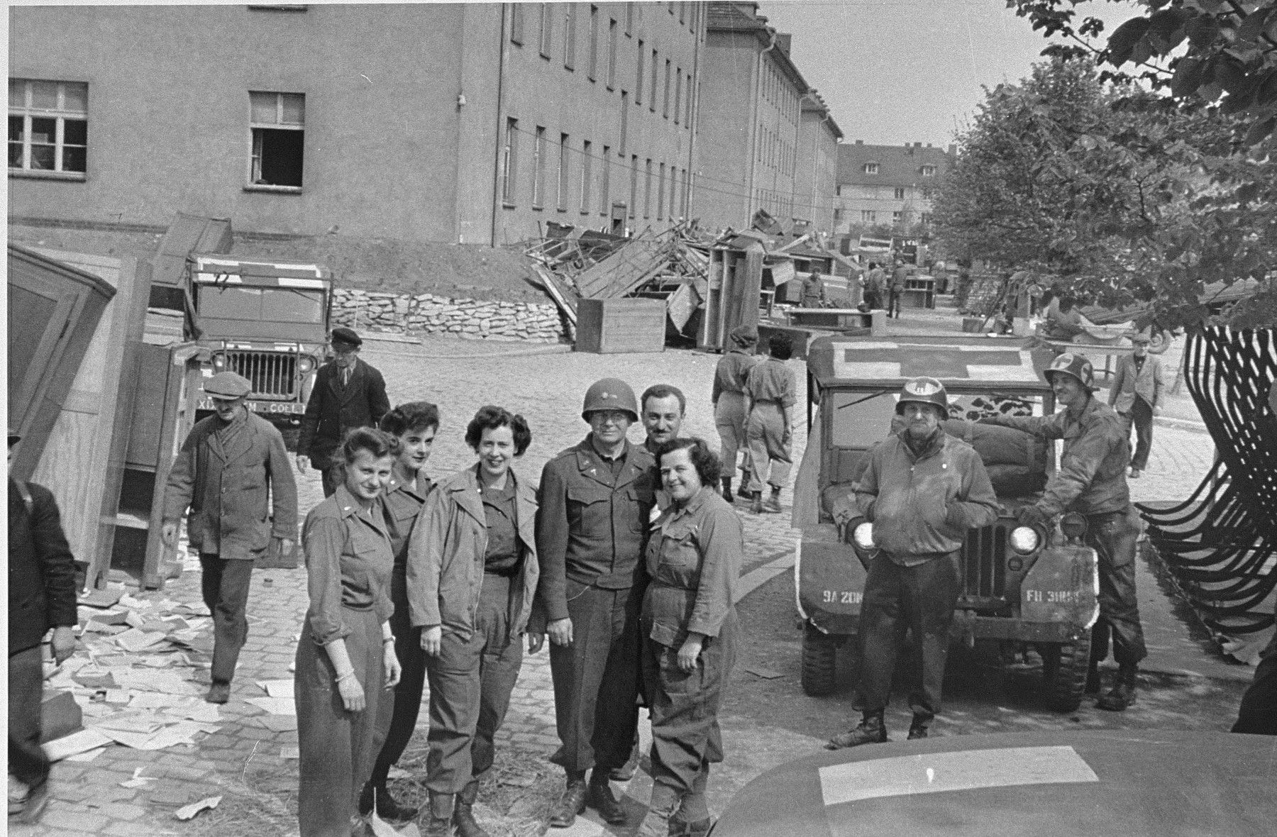 American medical personnel stand in front of a school that has been converted into a hospital for concentration camp survivors from Langenstein-Zwieberge.   Among those pictured is Francis A. Speer (third from the left, facing the camera).