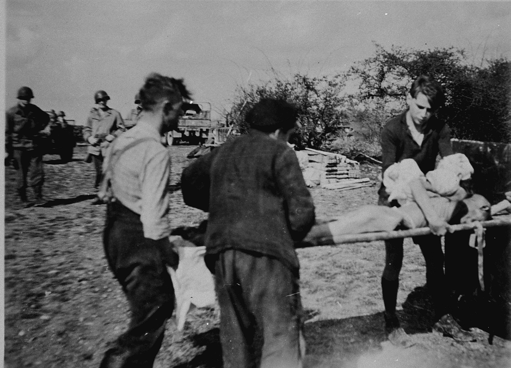German civilians from a nearby town load corpses onto a cart for transportation to a mass grave.