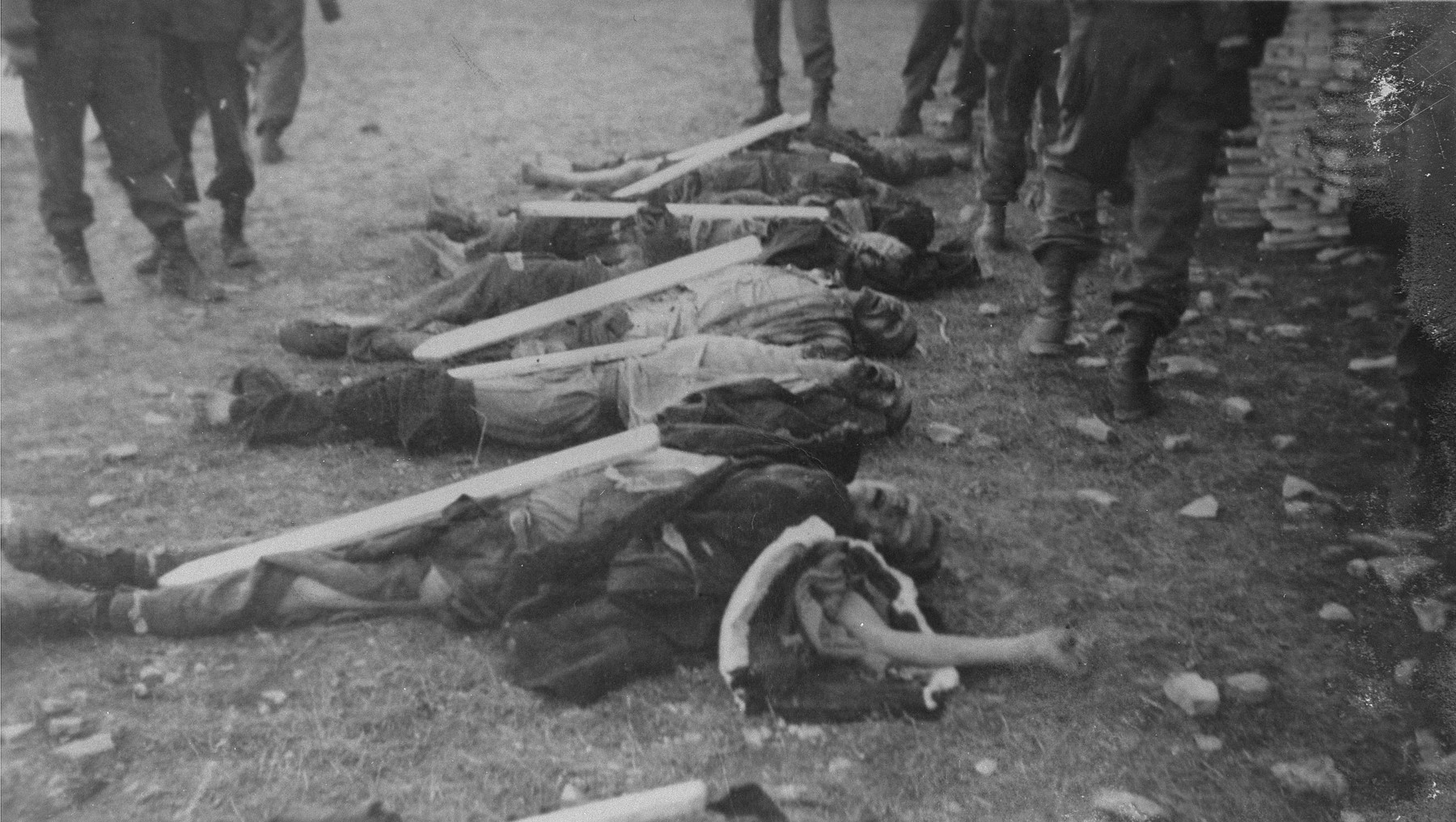 American troops prepare corpses found in Ohrdruf for burial.  The grave markers were inscribed with the prisoners' tattoo number.