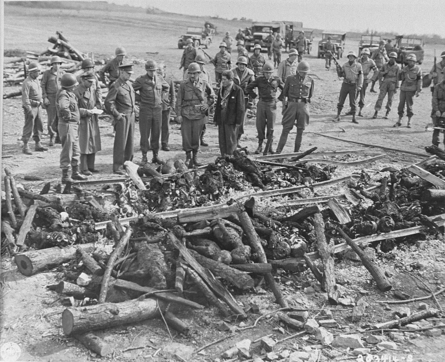 """While on an inspection tour of the newly liberated Ohrdruf concentration camp, General Dwight Eisenhower and a party of high ranking U.S. Army officers, including Generals Bradley, Patton, and Eddy, view the charred remains of prisoners that were burned upon a section of railroad track during the evacuation of the camp.  Also pictured is Jules Grad (second from the left taking notes), correspondent for the """"Stars and Stripes"""" U.S. Army newspaper and Alois J. Liethen of Appleton, WI, the mustached soldier who served as the interpreter for the tour of Ohrdruf.   The original Signal Corps caption reads, """"GENERAL EISENHOWER SEES NAZI  ATROCITIES.  Following discovery of a Nazi SS murder camp at Ohrdruf, Germany, by advancing troops of the Fourth Armored Division, Third U.S. Army, April 4, 1945, General of the Army Dwight D. Eisenhower, Supreme Commander-in-Chief Allied Expeditionary Force, went personally to the scene to inspect  evidences of atrocities.  He was accompanied by a party of high-ranking U.S. officers, including General Omar N. Bradley, Commanduing General of the 12th Army Group, and Lieutenant General George S. Patton, Jr., Commanding General of the Third U.S. Army.  American soldiers who seized the camp found the camp littered with the bodies of Czechoslovakian, Russian, Belgian and French slave laborers, slain because they were too weak and feeble to be evacuated.  In a shed, they found a stack of 44 naked, lime-covered bodies.  According to survivors, 3,000 to 4,000 prisoner had been killed by Nazi SS troops, 70 being slain just before arrival of the Americans.  Eighty survivors had excaped death or removal by hiding in the woods nearby.  They reported that an average of 150 died daily, mainly from shooting or clubbing.  The Nazi system was to feed prisoners on a crust of bread daily, put them to work on tunnelling projects until they were too weak to continue, then exterminate them and replace them with another 150 prisoners daily.  BIPPA              """