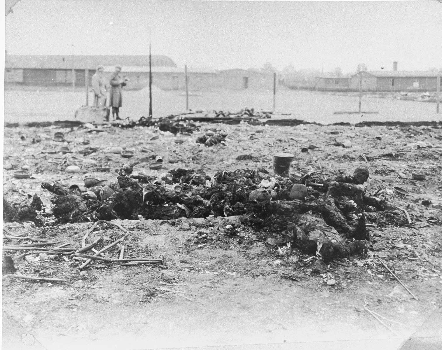 Two American soldiers inspect charred corpses in Leipzig-Thekla, a sub-camp of Buchenwald.