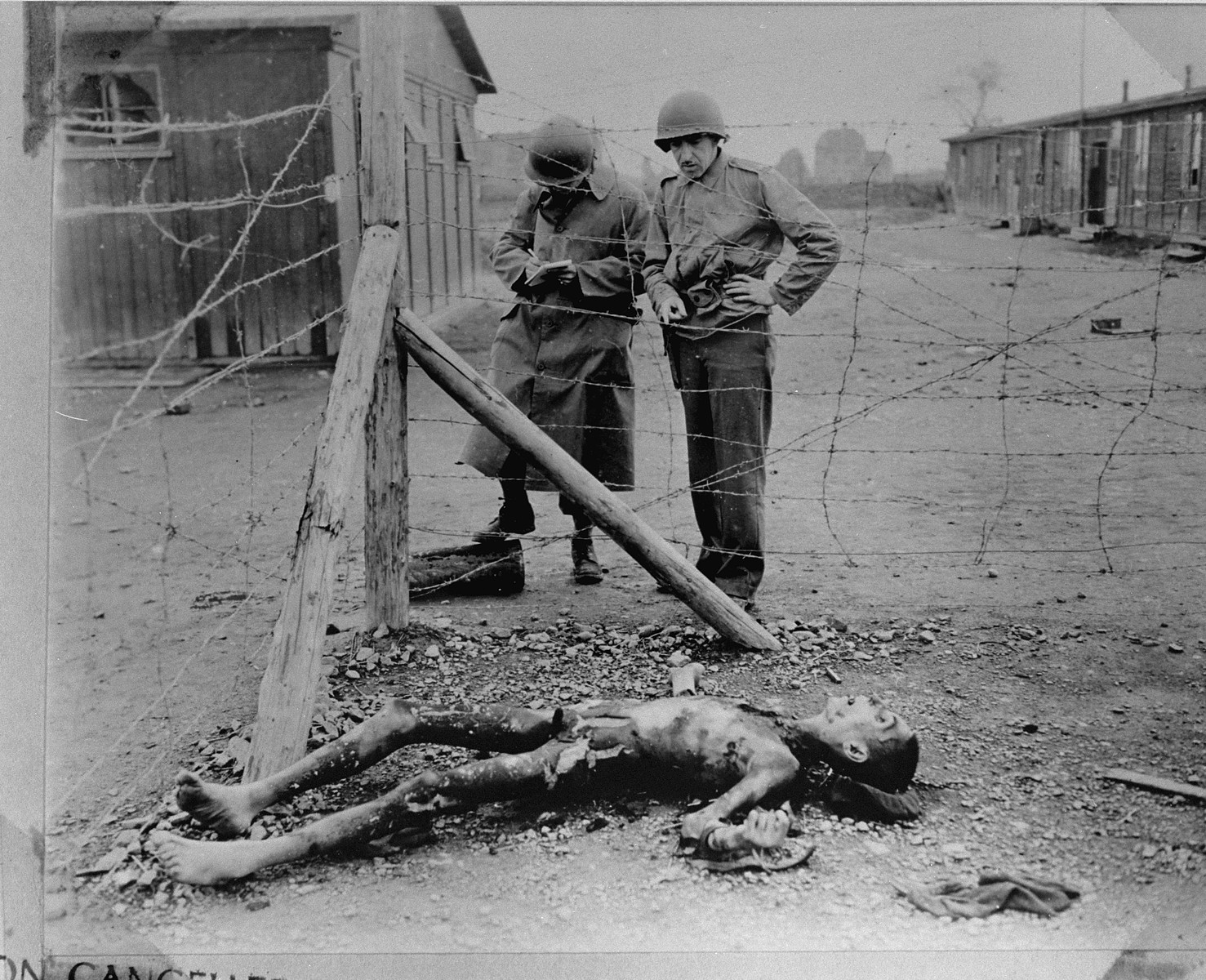 Two American soldiers conducting an investigation of Leipzig-Thekla, a sub-camp of Buchenwald, make notes while examining a corpse lying near a barbed wire fence.