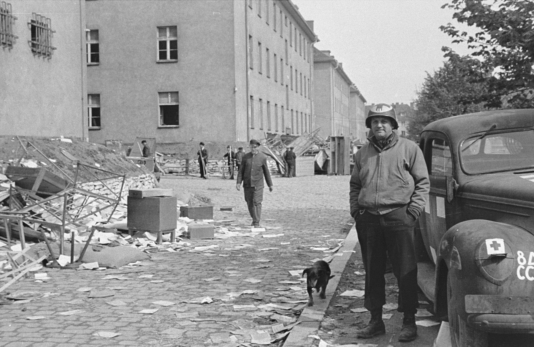 An American medical officer stands in front of a school that has been converted into a hospital for concentration camp survivors from Langenstein-Zwieberge.