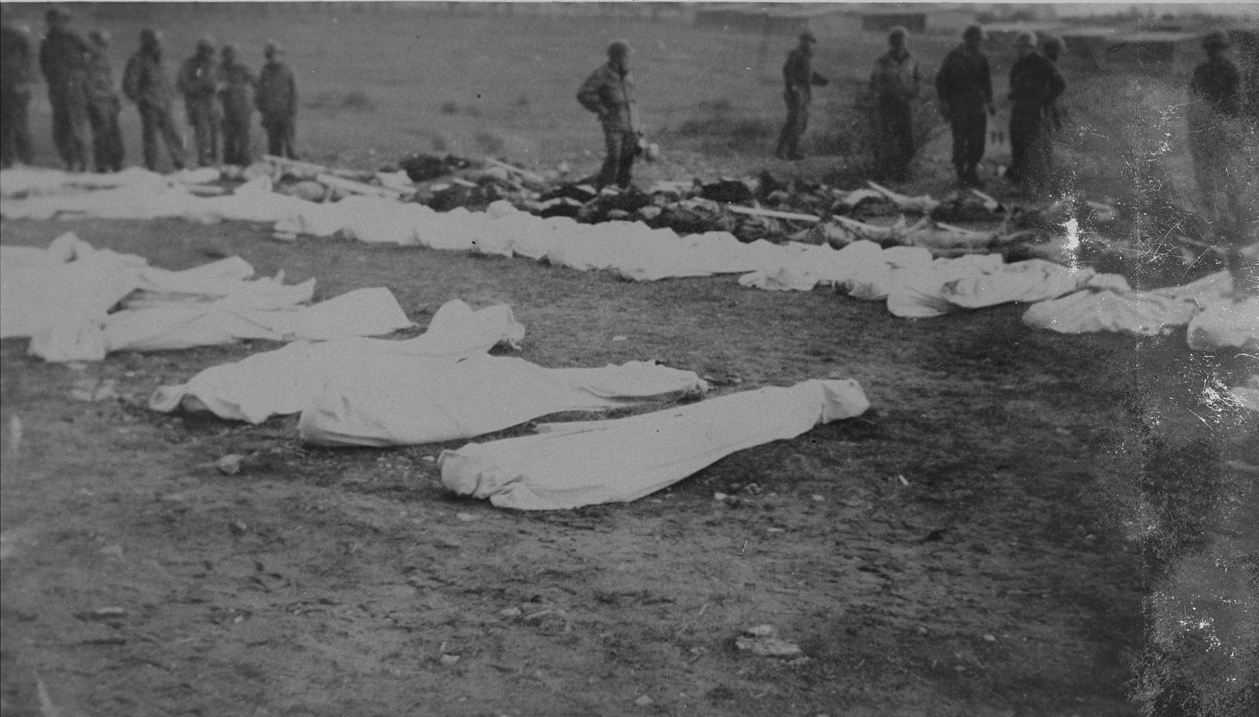American troops at the burial of corpses found in the Ohrdruf concentration camp.  Each corpse was assigned a numbered grave marker.