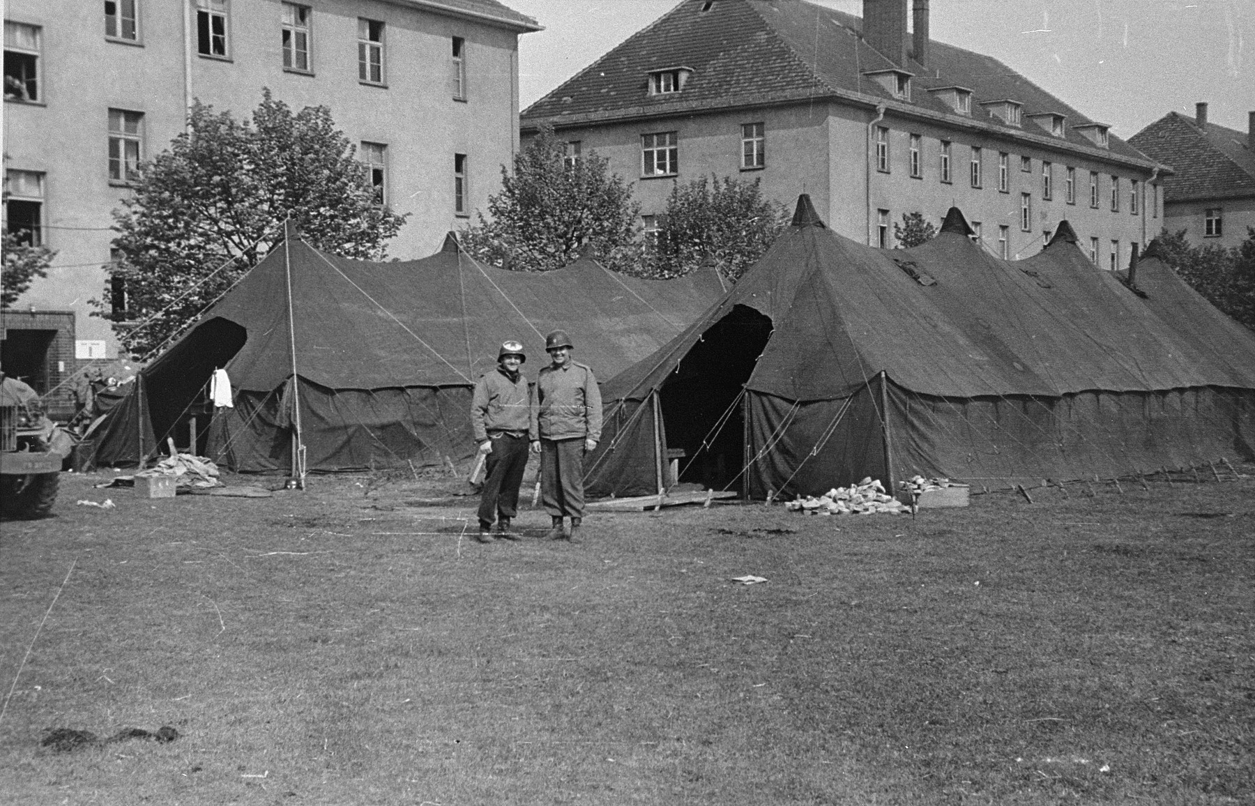 American medical personnel stand in front of two tents set up outside a school which has been converted into a hospital for concentration camp survivors from Langenstein-Zwieberge.