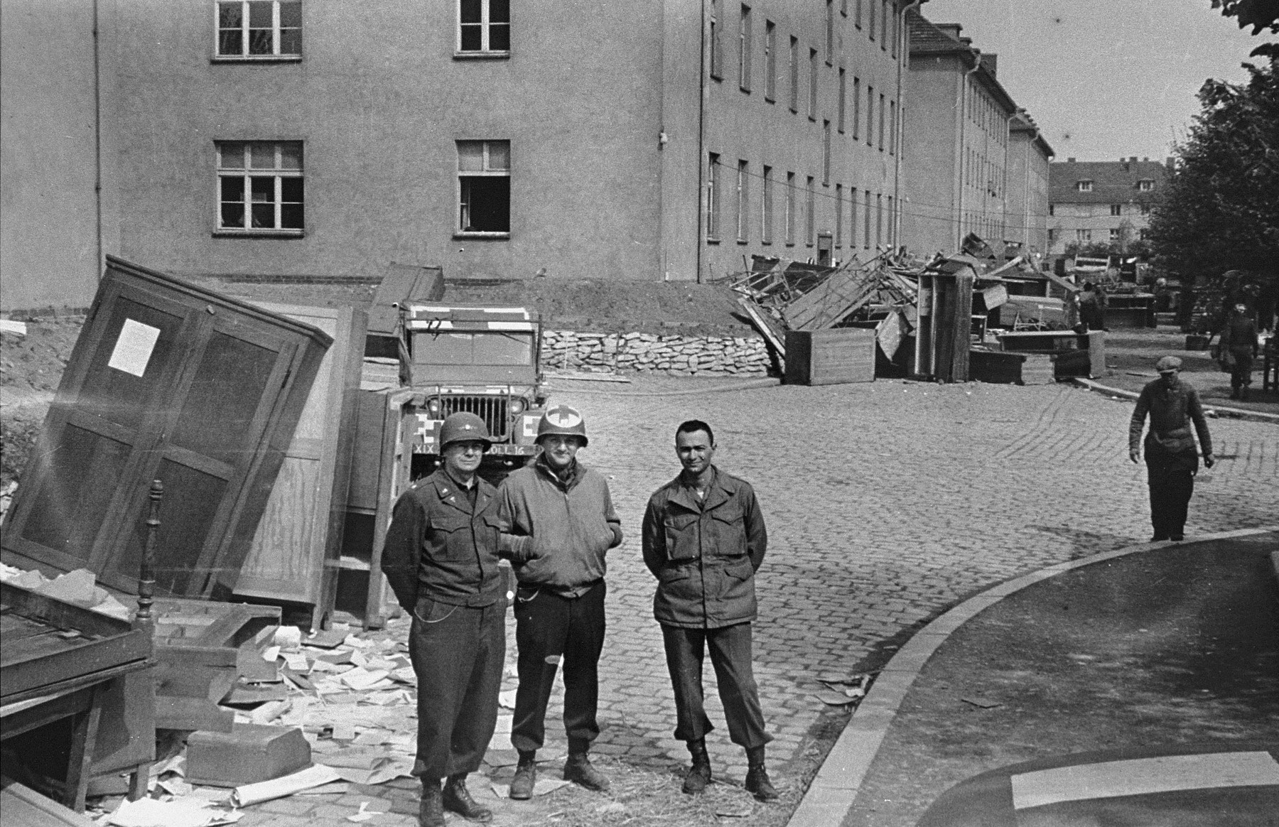 American medical personnel stand in front of a school that has been converted into a hospital for concentration camp survivors from Langenstein-Zwieberge.
