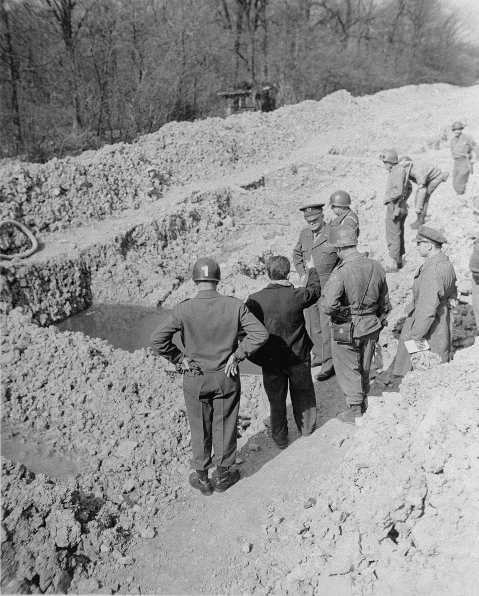 During an official tour of the newly liberated Ohrdruf concentration camp, an Austrian Jewish survivor points out the sites of mass graves to Generals Dwight Eisenhower and Omar Bradley.
