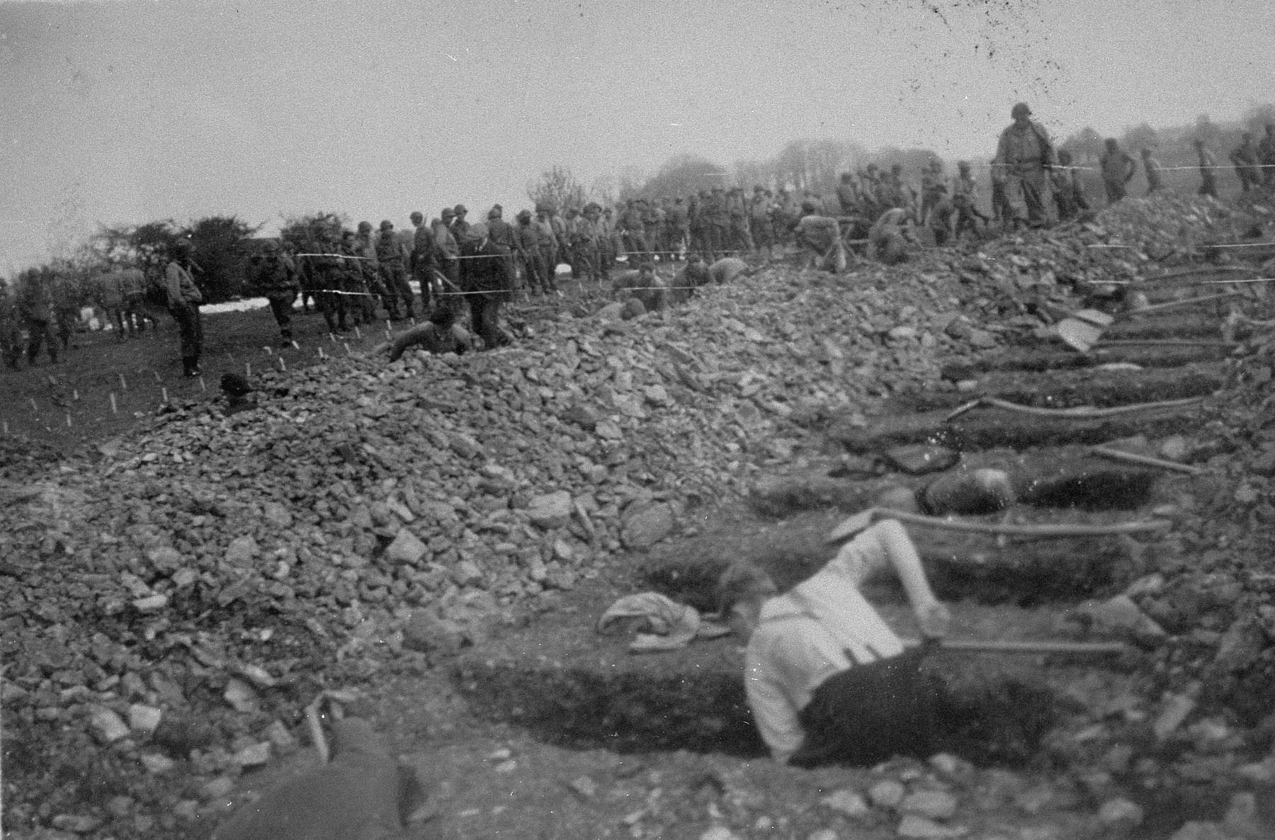 German civilians conscripted from nearby towns dig graves for prisoners killed in Ohrdruf as American soldiers look on.