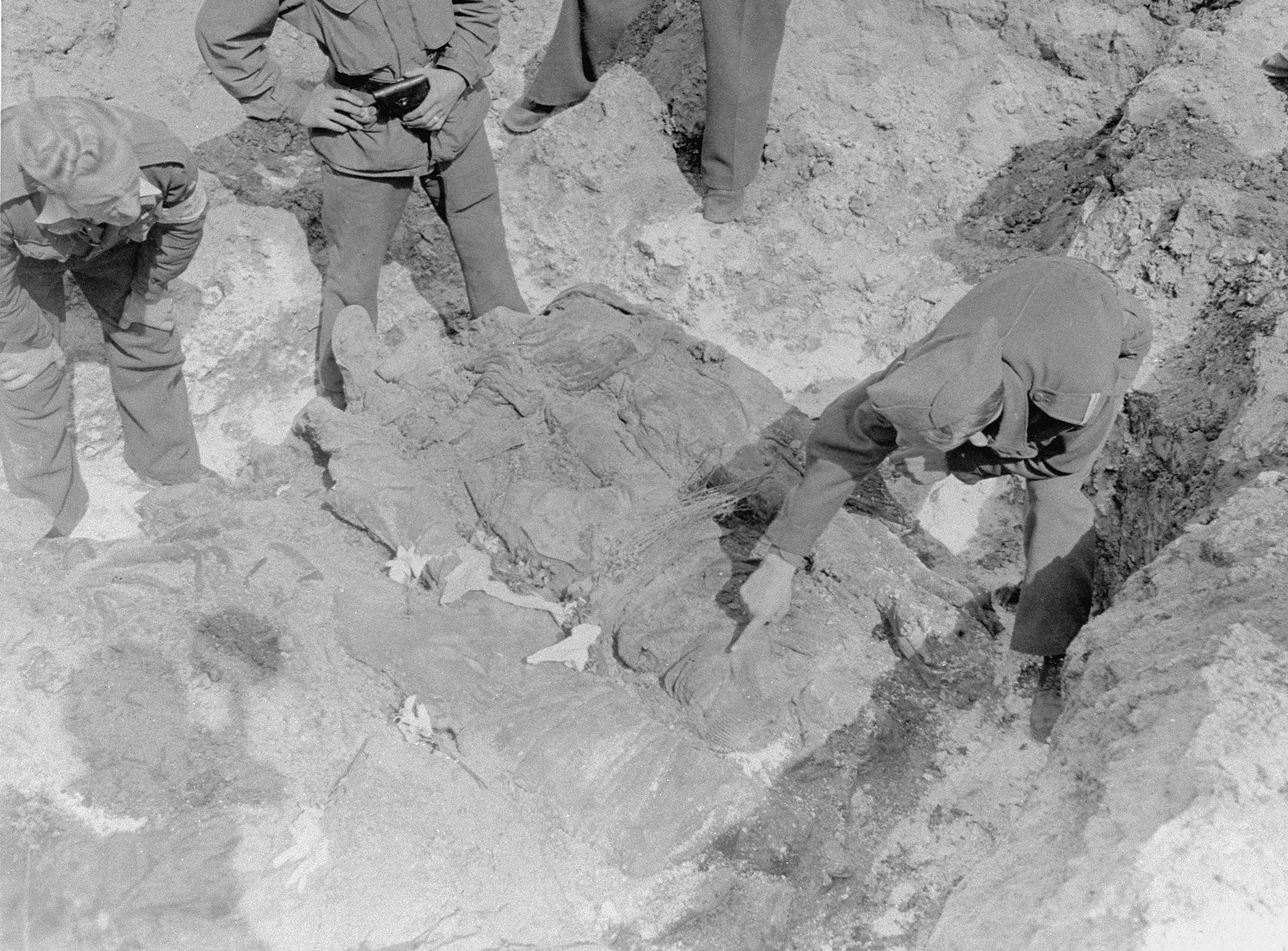 American investigators study corpses exhumed from a mass grave in Berga-Elster, a sub-camp of Buchenwald.