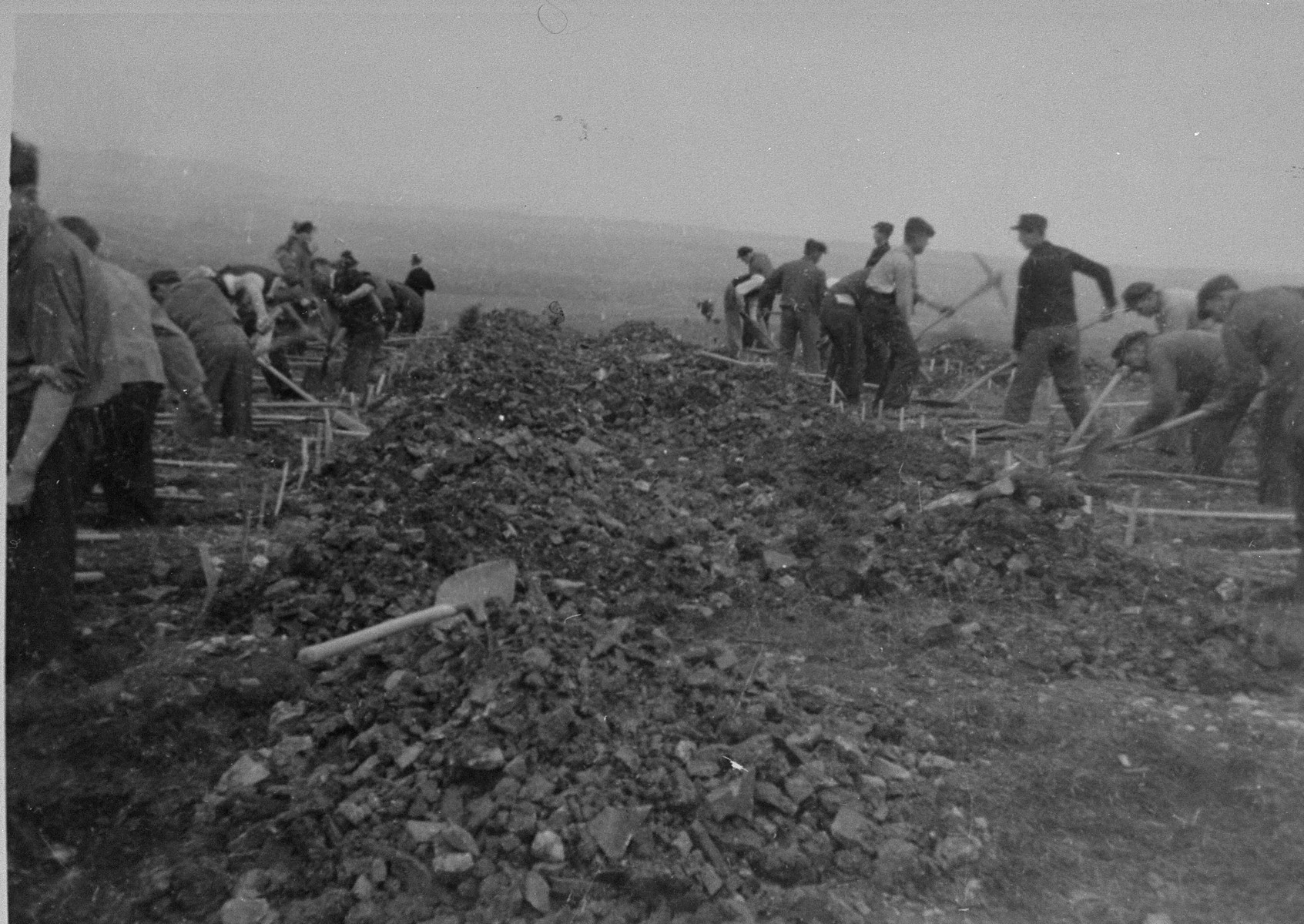 German civilians conscripted from the area surrounding Ohrdruf dig graves for corpses found in the camp by American soldiers.