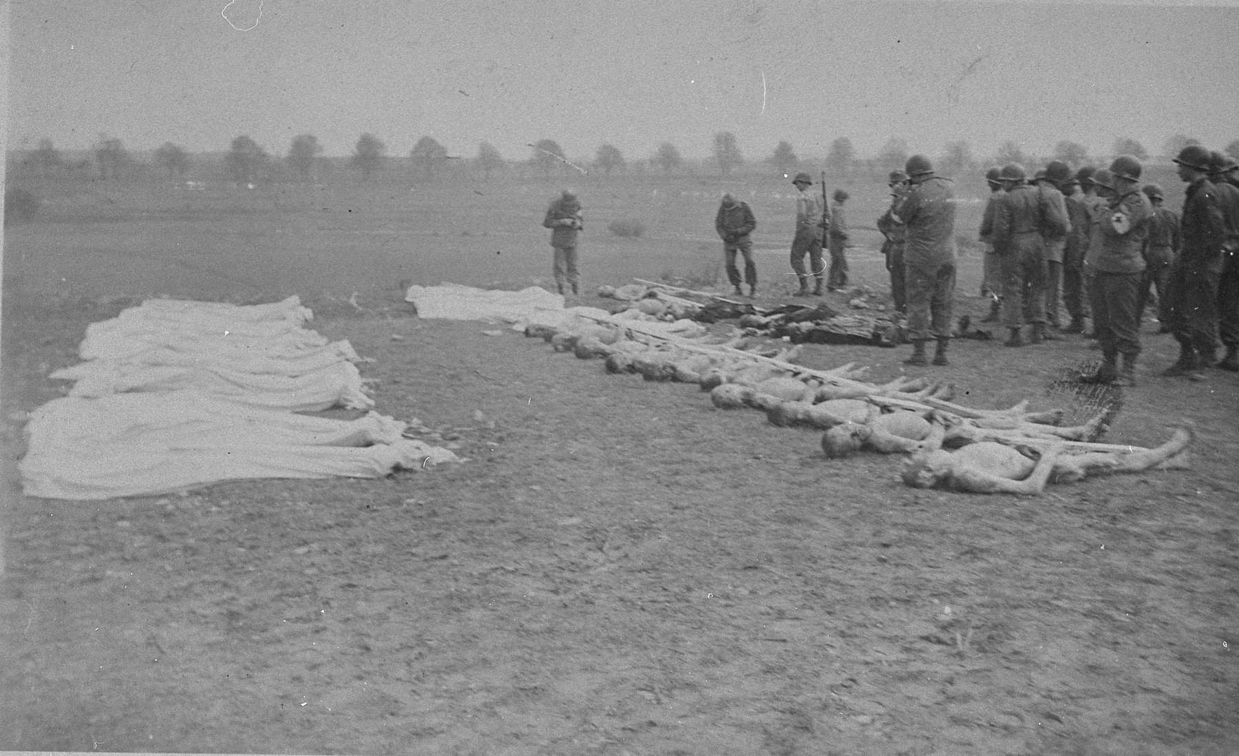American soldiers look on as corpses from Ohrdruf are prepared for burial.  Each corpse was assigned a numbered grave marker.