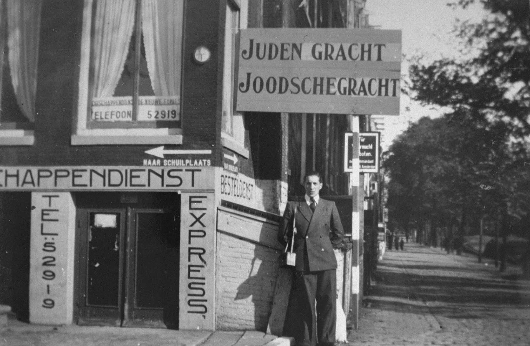 Samuel Schryver poses beneath a sign indicating the entrance to the Jewish quarter of Amsterdam.