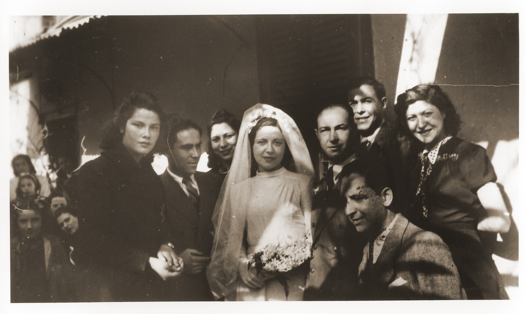 The bride and groom, Victoria Sarfati and Yehuda (Leon) Beraha, pose with family members at their wedding.  Their marriage was hastily arranged two months before their deportation so that they might be able to stay together.  The couple perished in Auschwitz.