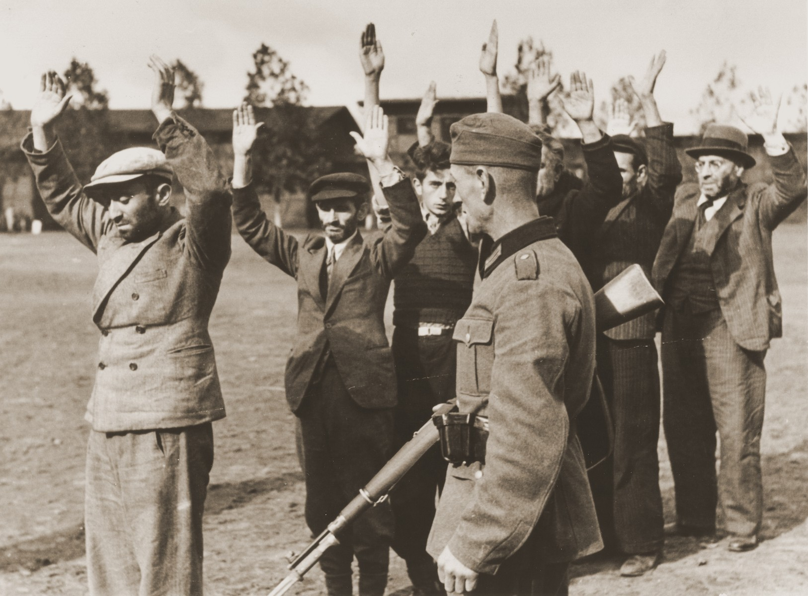 A German soldier guards a group of Poles and Jews who have been rounded-up and forced to stand in a line with their arms raised.