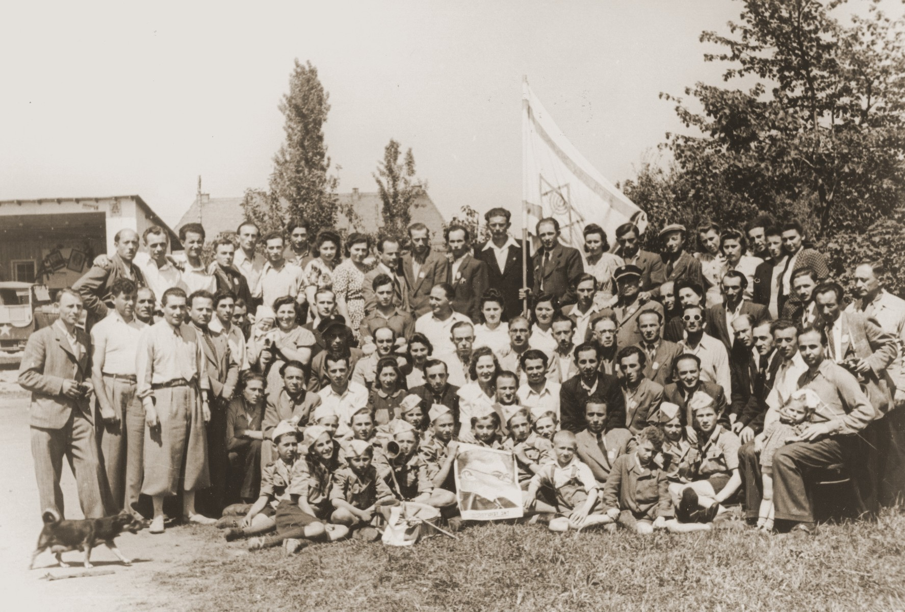Group portrait of members of Betar Zionist youth movement in Neu Freimann displaced persons camp holding a Zionist flag and portrait of Zev Jabotinsky.  Among those pictured in the second row are the pricipal Mrs. Spektor and Moshe Blautal.