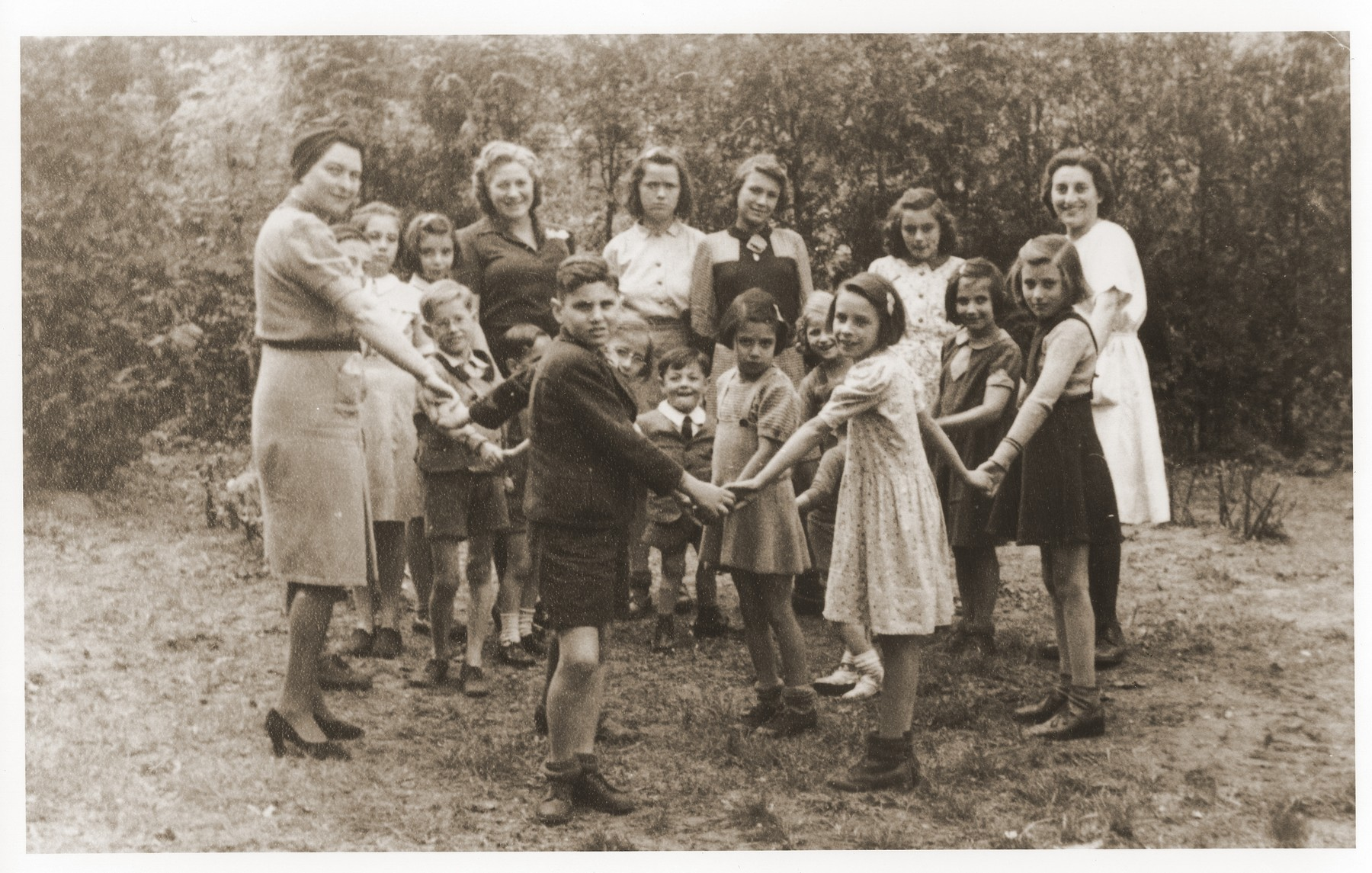 Children and teachers pose in a circle in the yard of the Lueneburg children's home.