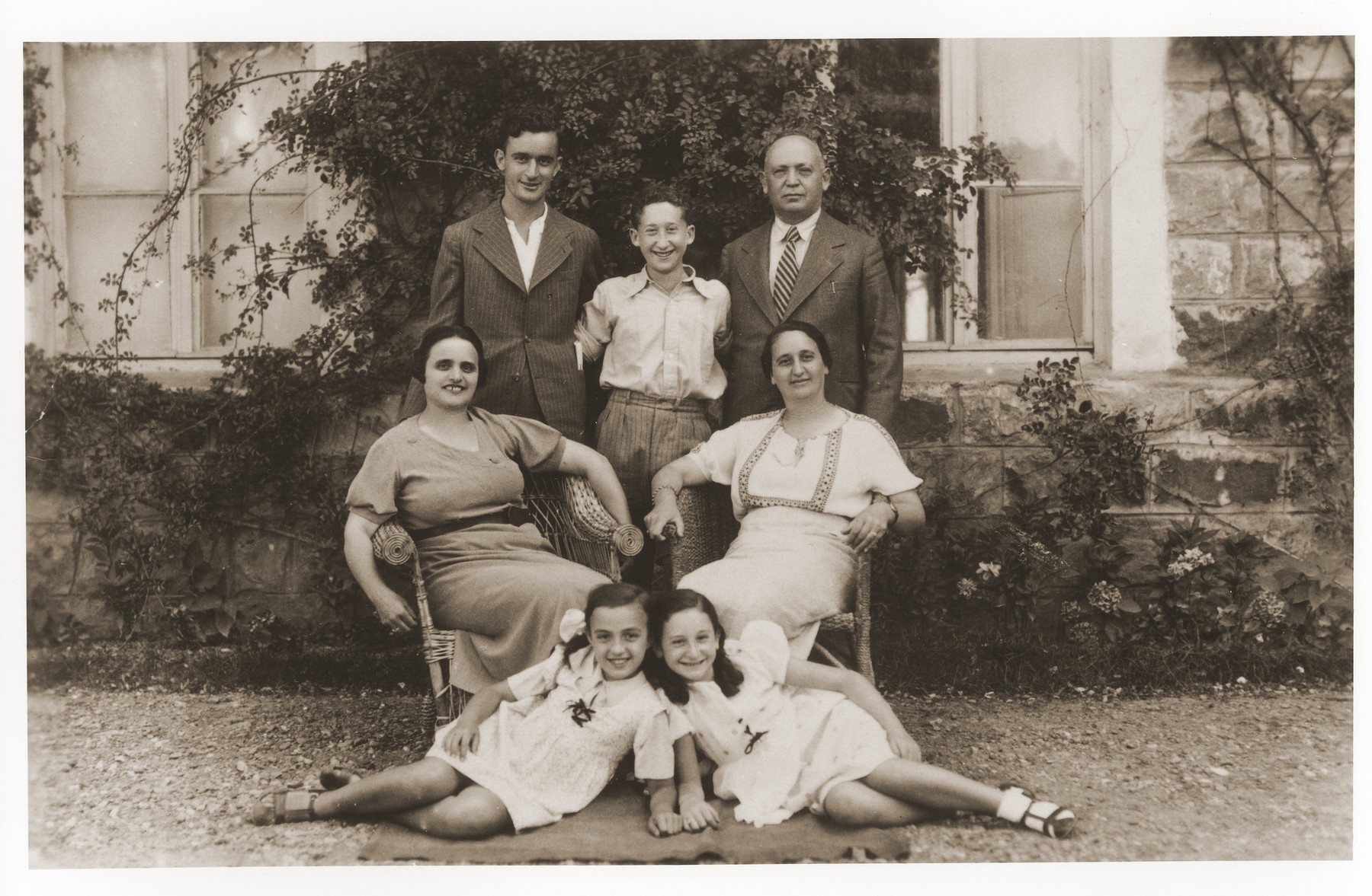 Portrait of the Amarillo family outside their home in Salonika.  Pictured in front, from left to right front are, Tillie Amarillo and Sarika Yahiel.  Seated behind them are their mothers Louisa Bourla Amarillo and Regina Amarillo Yahiel.  Standing in back are, Saul Amarillo, Isaccino Yahiel and Isaac Yahiel.  Tillie Amarillo survived the war in hiding and married Dr. Rene Molho, a survivor of Auschwitz, in March 1946.