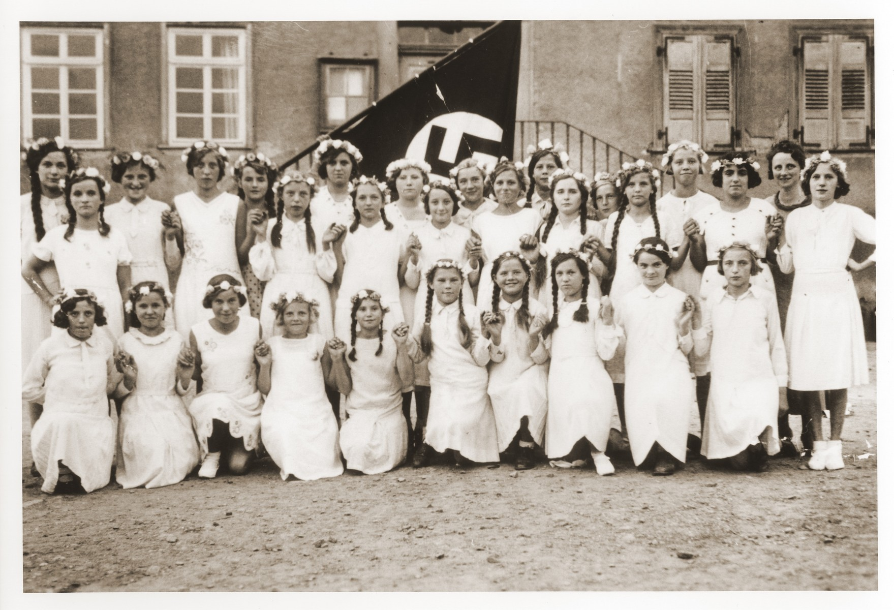 Group portrait of German girls posing outside their school in front of a Nazi flag.  Among those pictured is Lilli Eckstein six months before she was expelled from the school for being Jewish.