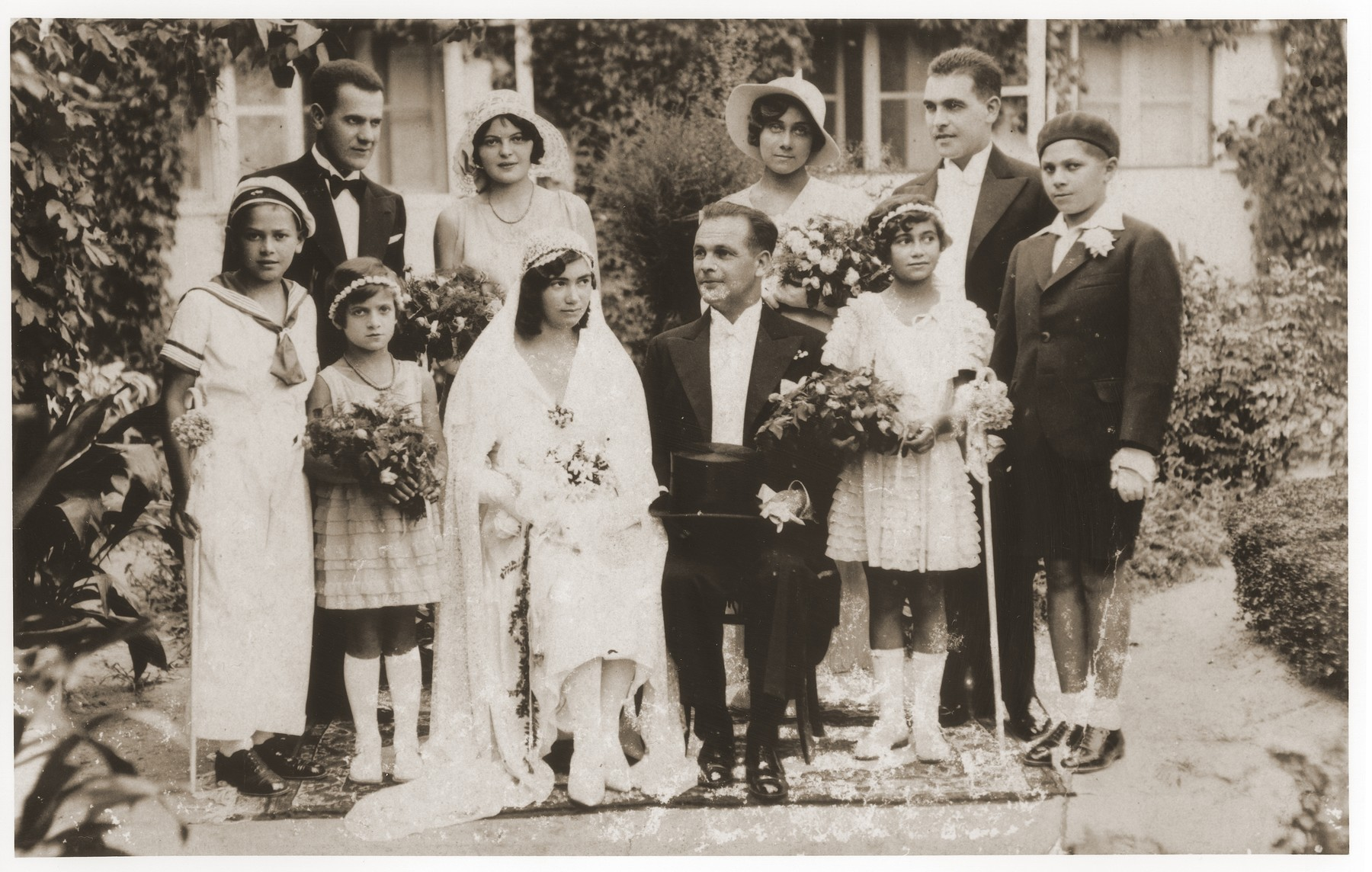 Wedding portrait of Magda Shiller and Miklos Blauhorn taken in the Shiller's back yard.   Pictured in the front row from left to right are, Ivan Singer, Ana Singer, Magda Shiller, Miklos Blauhorn, Olga Shiller and Yelinek Josko.  Behind Ivan is Gabor Schwartz.  All those pictured except Ivan perished during World War II.