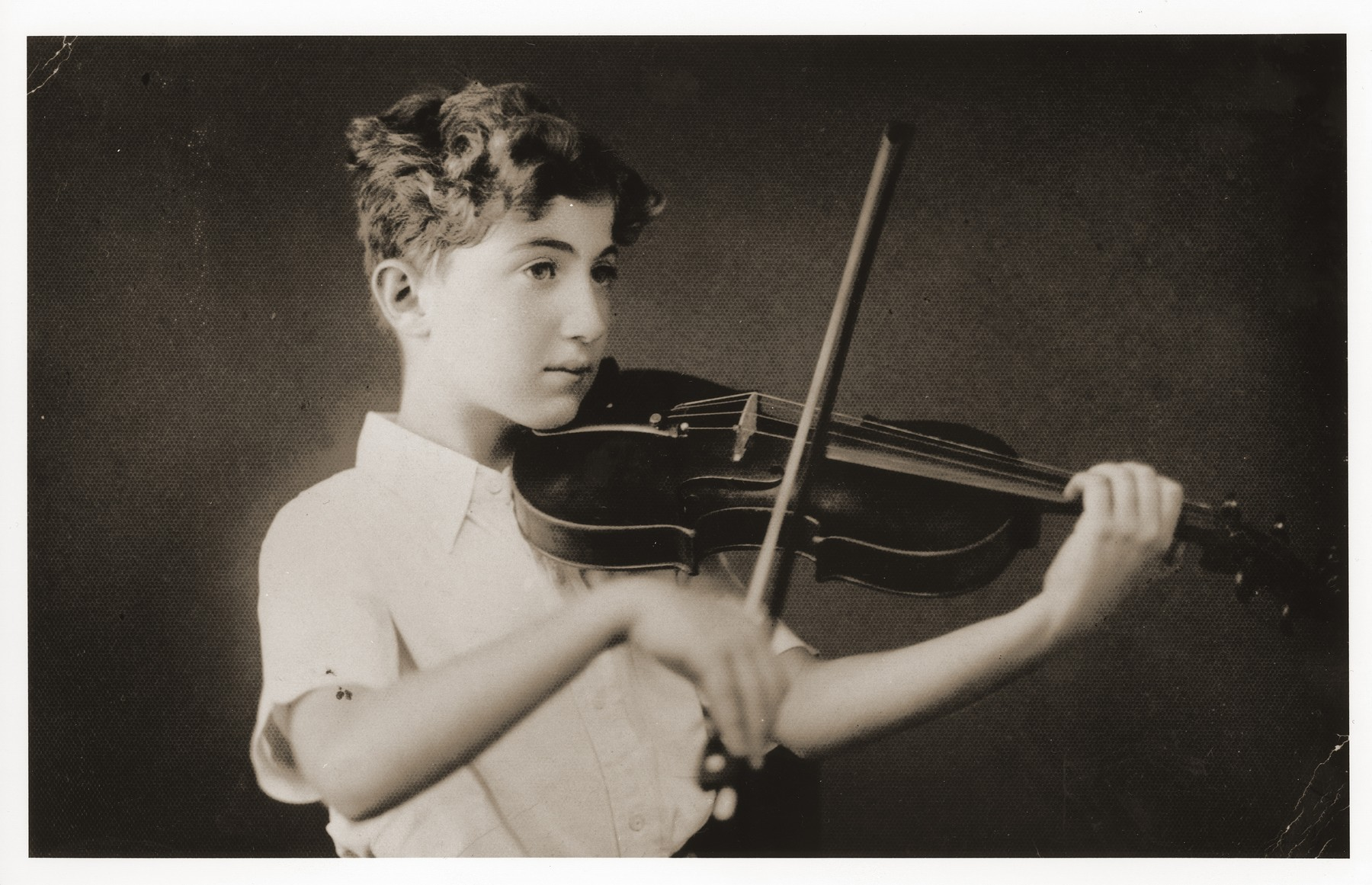 The eleven-year-old German Jewish refugee, Helmut Stern, practices the violin in his home in Harbin, China.
