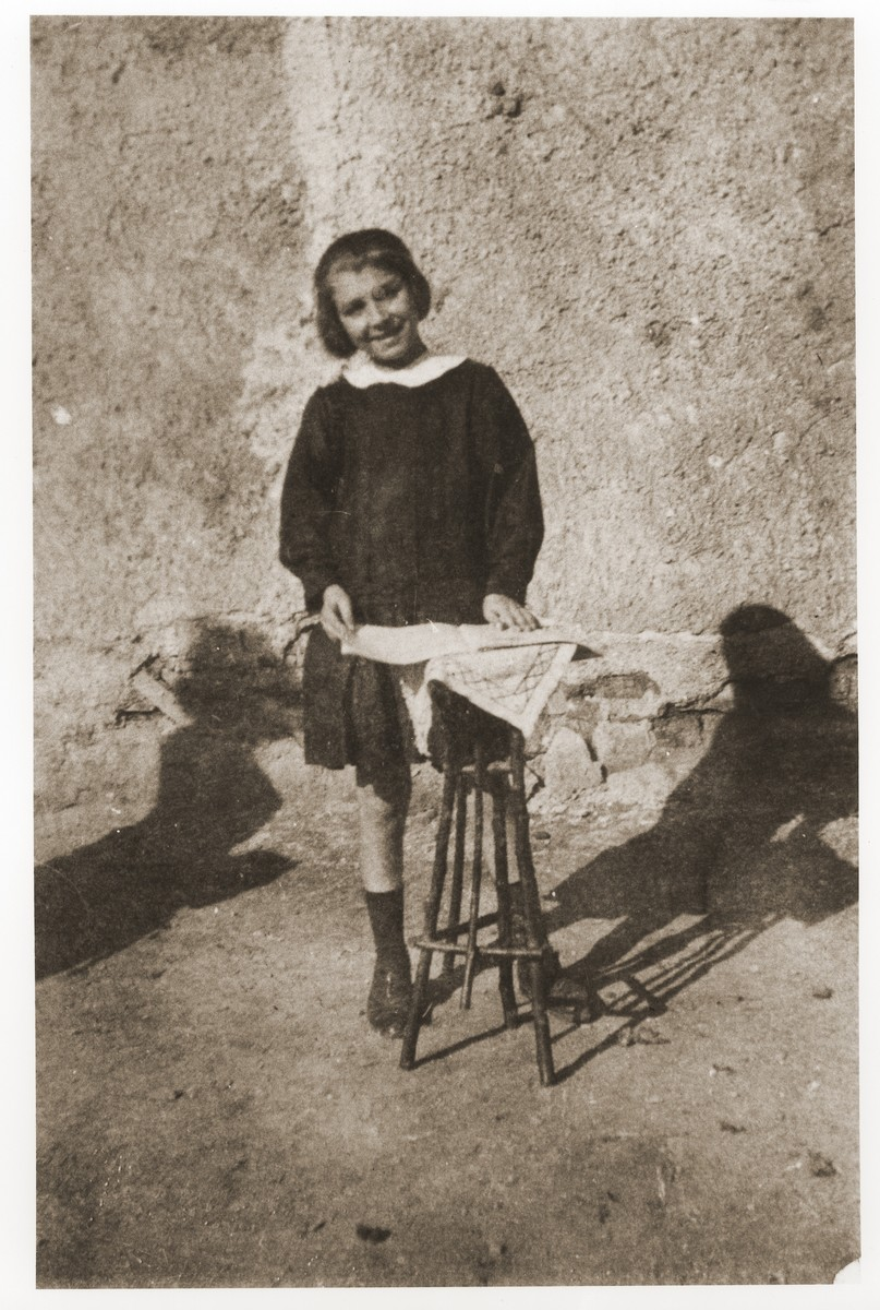 Miriam Beraha stands by a small table covered with a cloth that she made by hand.
