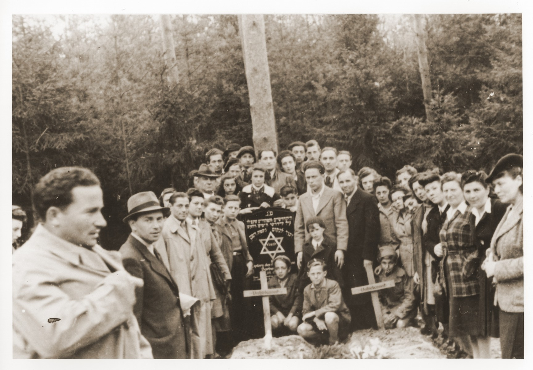 A large group of Jewish displaced persons poses next to two graves marked with wooden crosses in Lueneburg.