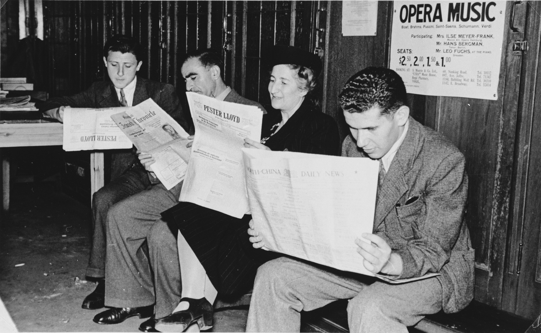 """Four Jewish refugees read copies of the Hungarian German language newpaper, """"Pester Lloyd,"""" published in Budapest, in the waiting room of the International Committee for European Immigrants in Shanghai.  One photograph from a second International Committee album prepared for I.C. secretary Paul Komor."""