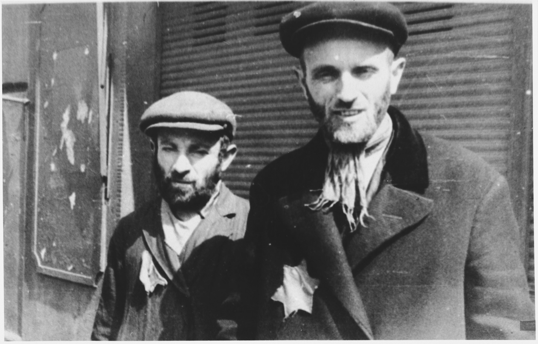 Two Jewish men wearing yellow stars stand in front of a shuttered store in an unidentified ghetto in Poland.