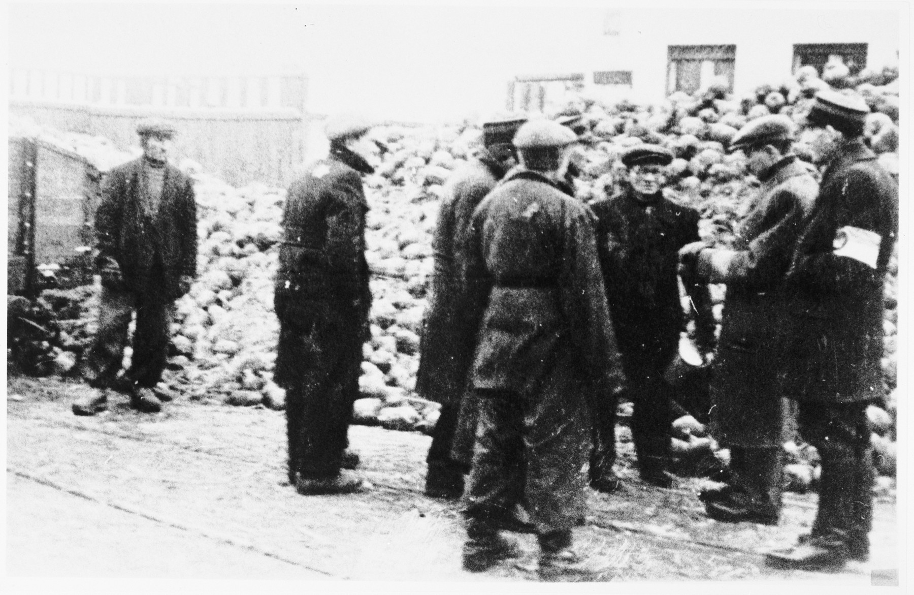 Jewish police stand with a group of laborers in front of a large pile [of food?] in the Lodz ghetto.