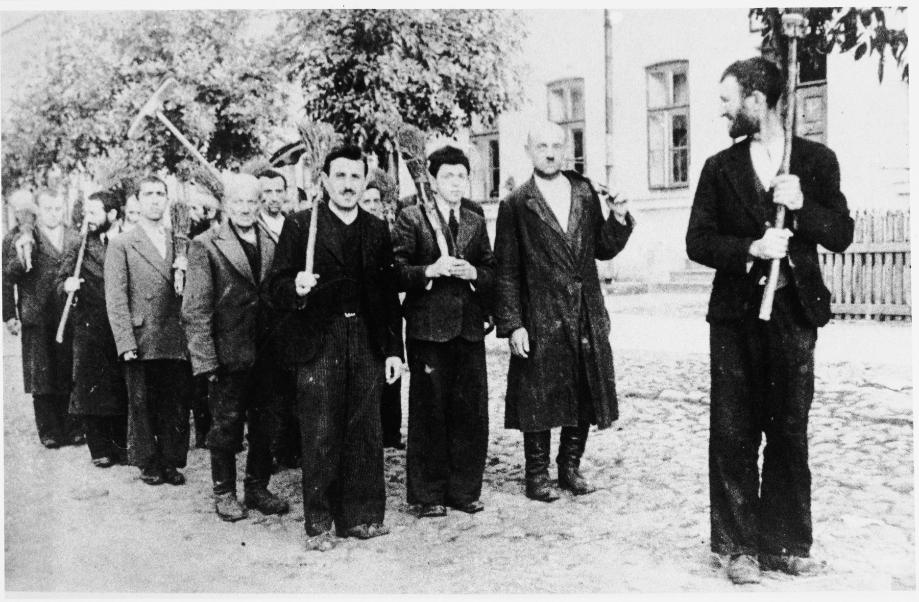 A column of Jews line up with brooms for forced labor in an unidentified ghetto.