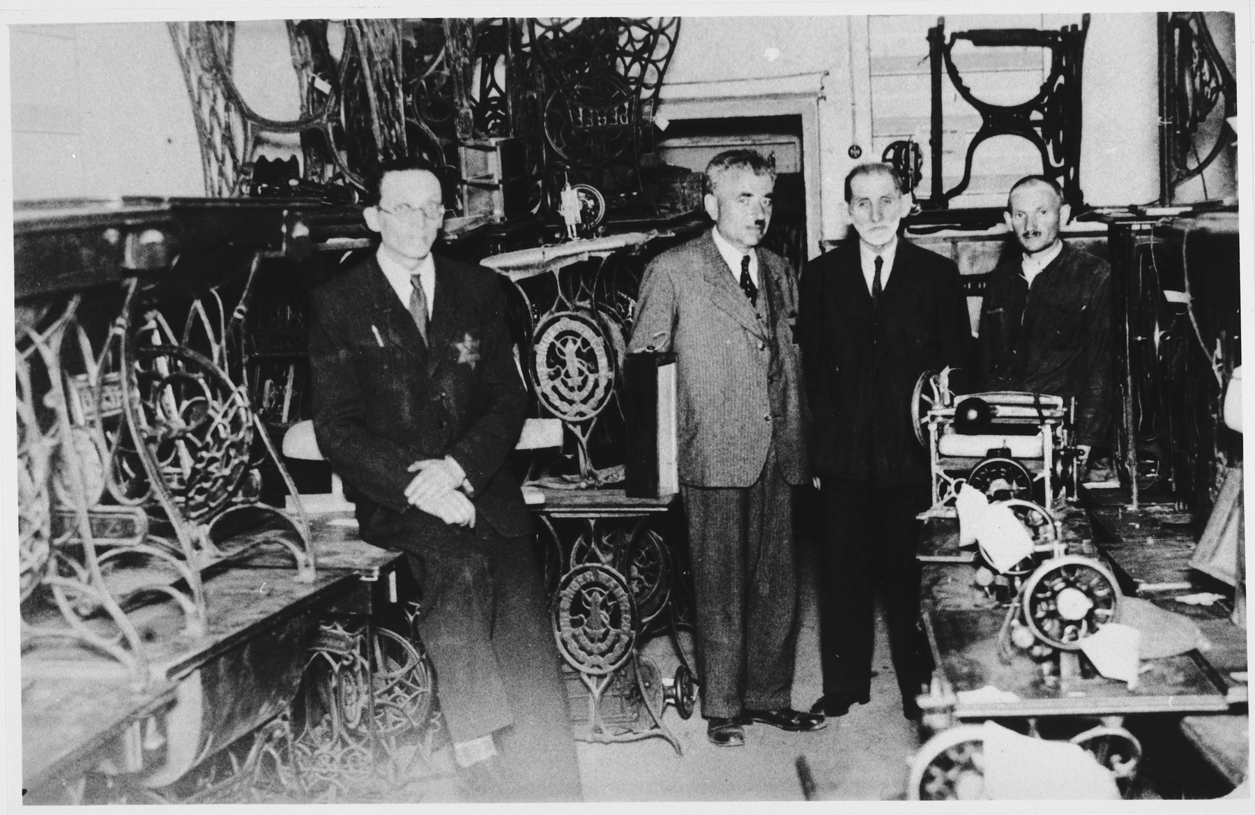 Four men wearing Jewish stars pose in a ghetto workshop filled with sewing machines.