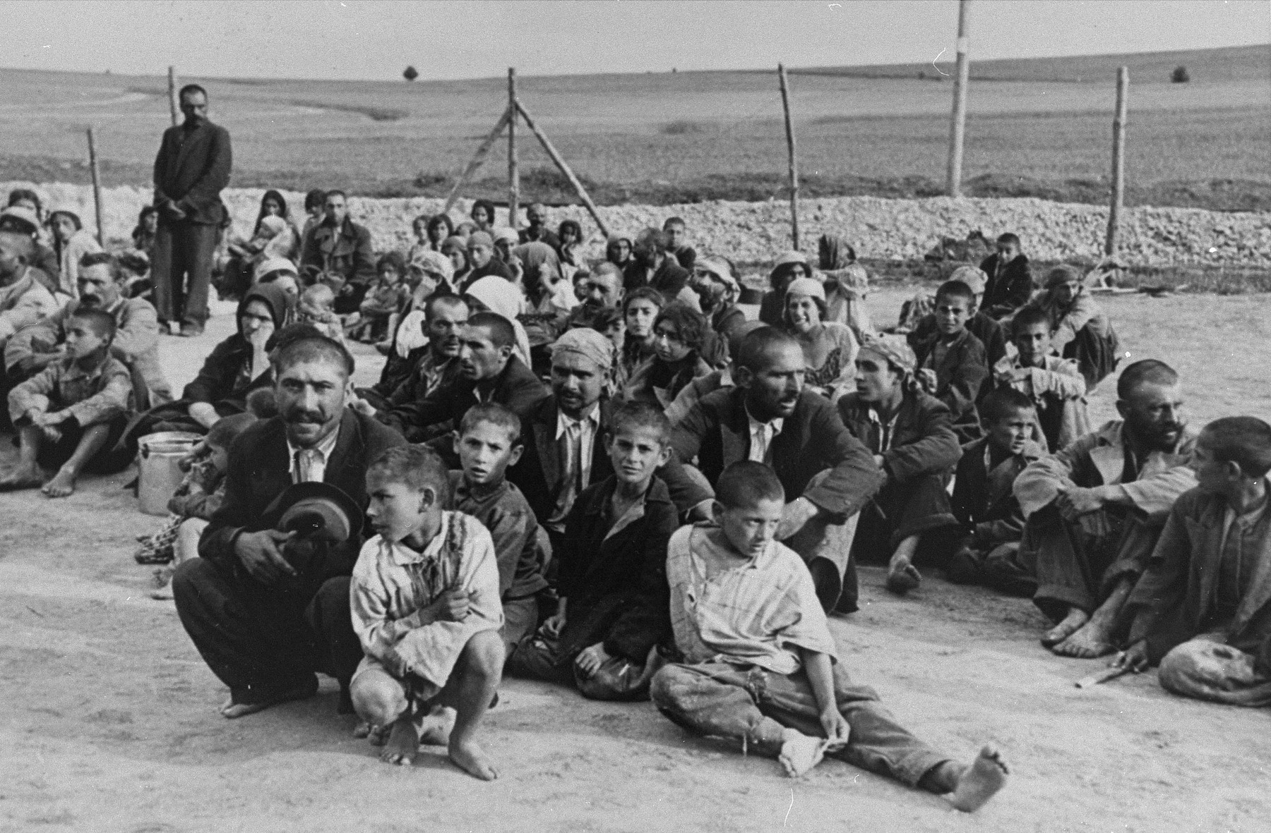 A group of Gypsy prisoners, awaiting instructions from their German captors, sit in an open area near the fence in the Belzec concentration camp.