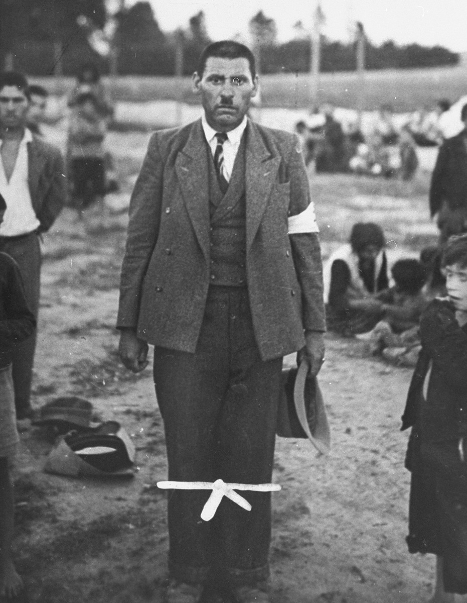 Portrait of a male Romani (Gypsy) prisoner wearing an armband.  Behind him Gypsy families sit in an open area within the fenced-off boundaries of the Belzec concentration camp.   The prisoner may be Jozef Kwiek, the self-proclaimed King of Polish Gypsies.