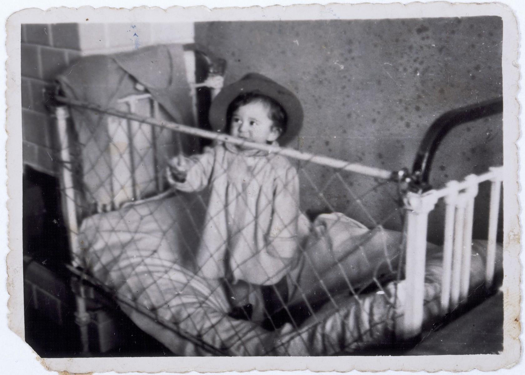 Jurek Kaiser standing in his crib in the Kielce ghetto.