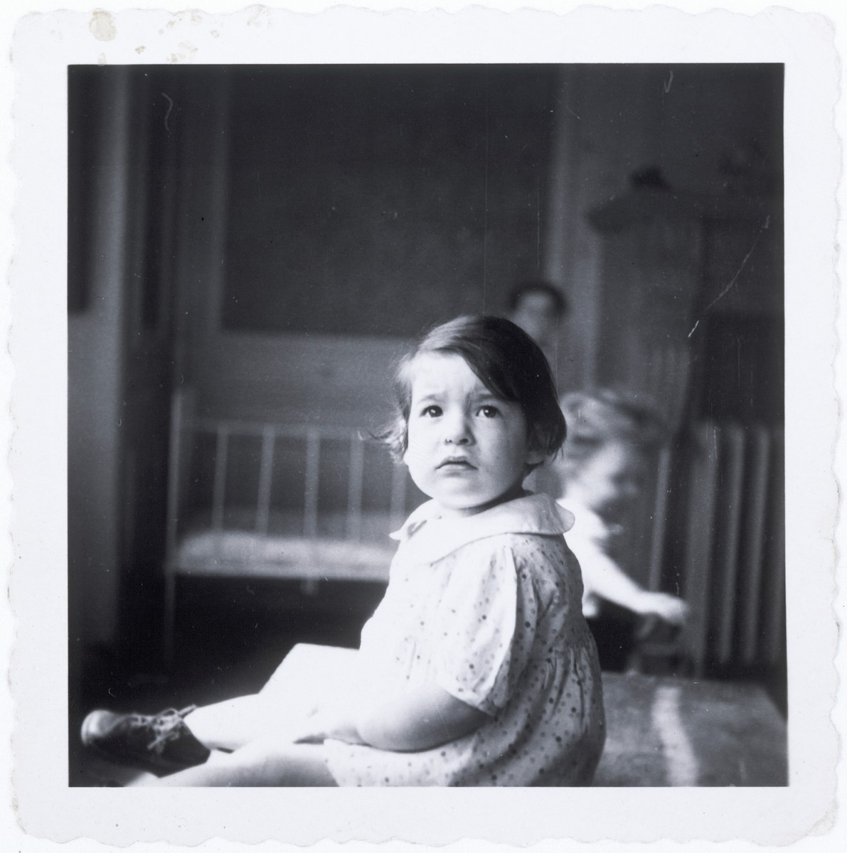 A young girl sits in the Baron de Castro home, a home for Jewish infants who are waiting for their families to claim them, or to be adopted.  Pictured is Jeannette Schindelheim (Oselka-Korn).  In the background is Jacques Weisser.  Jeannette's parents were deported and killed. She was adopted by a maternal aunt in the United States.
