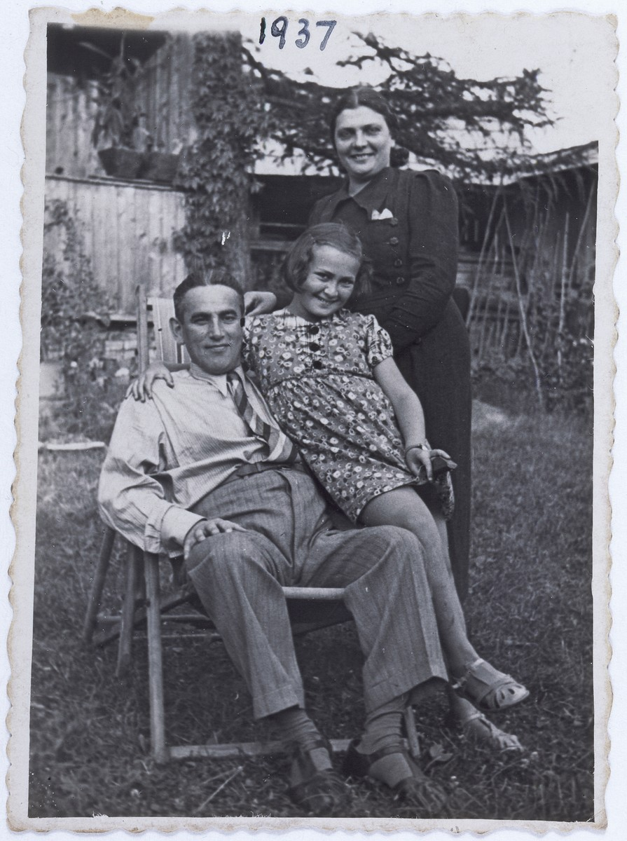 Members of the Kwar family pose outside on a lawn chair.  Pictured from left to right are Benzion, Roza and Ester Kwar.