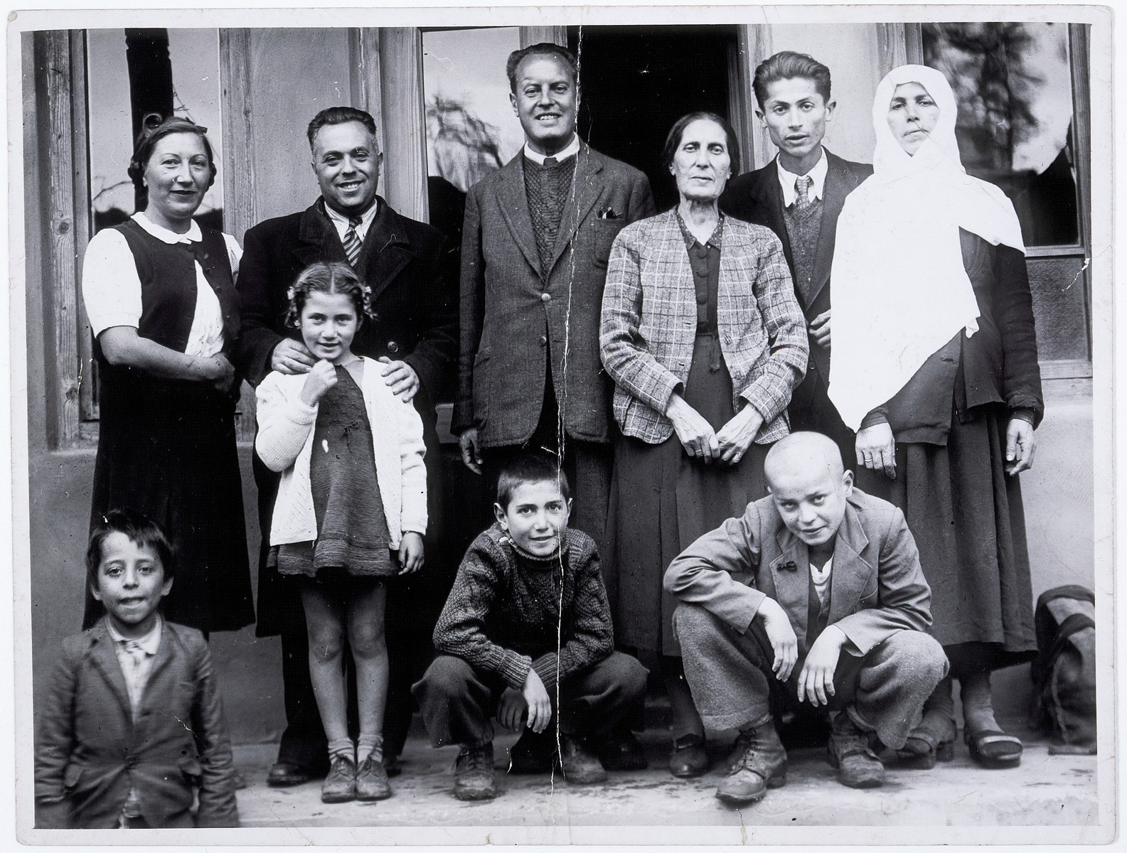 Group portrait of members of the Franses family, a Jewish refugee family from Skopje, Macedonia, with the Albanian family (the Kasapis) that sheltered them in Tirana, Albania.  Pictured in the top row from left to right are: Vinka Franses, Mr. Batino (a wealthy Albanian Jew from Tirana), Mois Franses, Ester Franses, Hamdi Kasapi, Mrs. Kasapi.  The children in front of them are: a neighbor's child, Eni Franses, Marcel Franses, and Josip Kasapi.