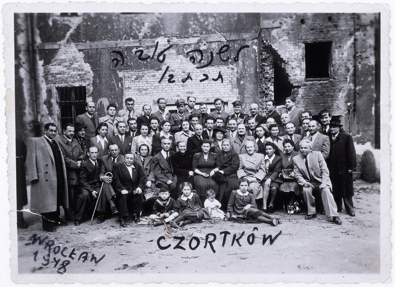 "Group portrait of survivors from the Jewish community of Czortkow, who are attending a memorial service in Wroclaw, Poland.  Across the top of the photograph is written, ""Happy New Year 1948.""  Among those pictured are Lola Kaufman (front row, right) and Abraham Trajner (Treiner) (back row, second from the right)."