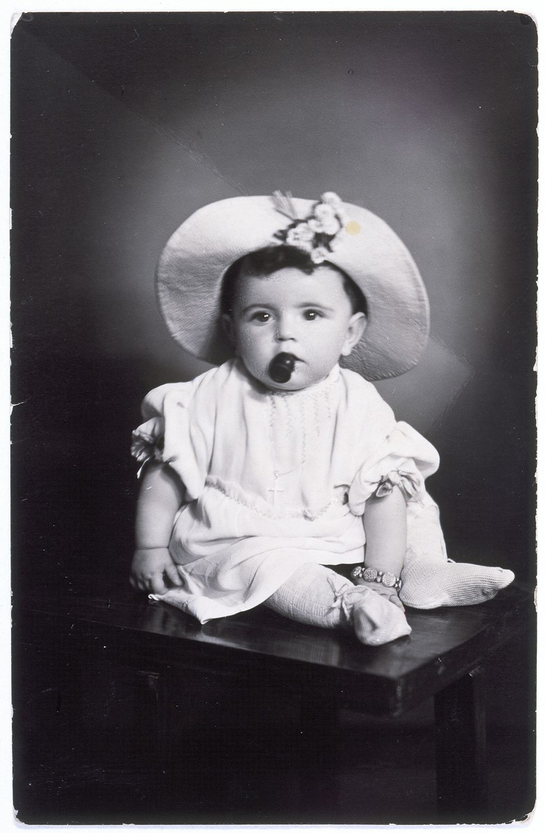 A studio portrait of Anita Kuenstler taken while she was in hiding at the age of two.  She poses in a hat while also wearing a chain with a cross around her neck.