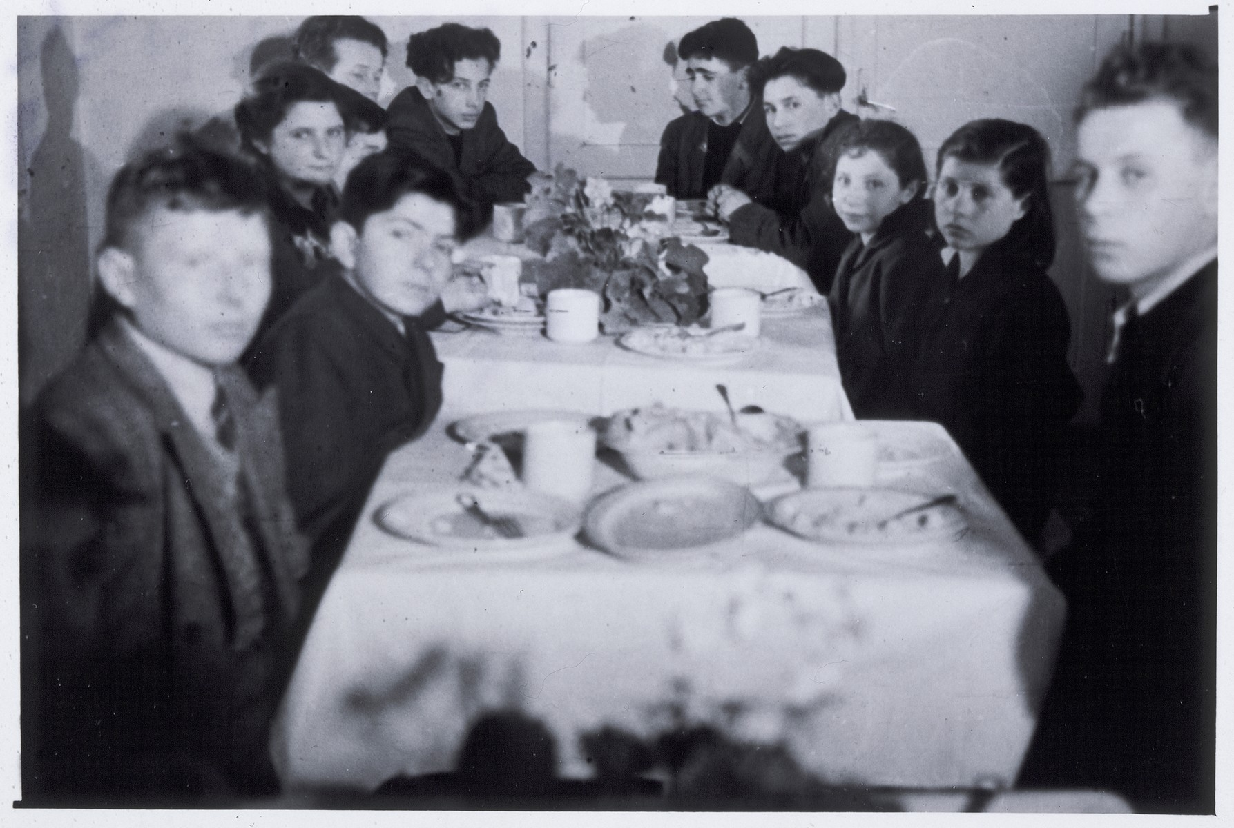 Children sit at a table in the orphanage at Helenowek.