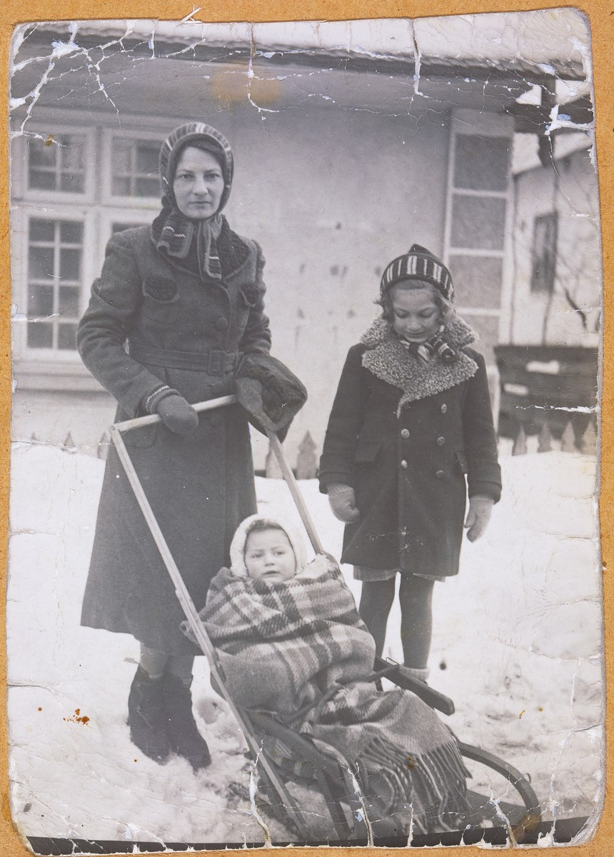 Olga Litman walks down a snowy street with her two daughters.