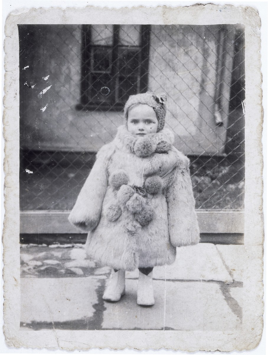 Portrait of three-year-old Estera Horn wrapped in a fur coat .