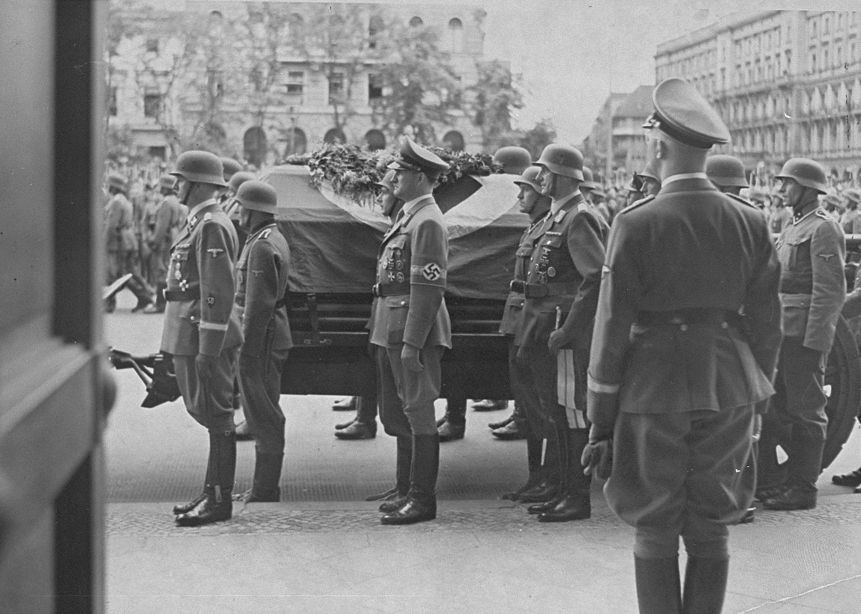 Reichsfuehrer-SS Heinrich Himmler looks on as Reinhard Heydrich's casket is carried out from the Reich chancellery for burial.