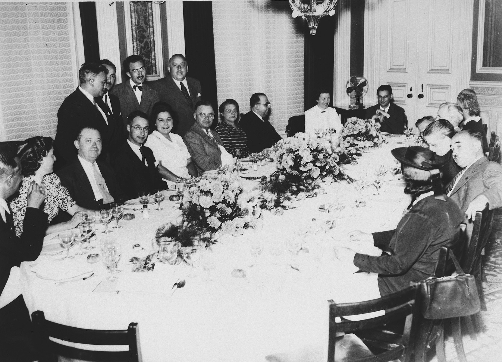 Members of various Jewish welfare organizations operating in Lisbon to rescue European Jewish refugees, are seated around a banquet table at a hotel in Lisbon.  Among those pictured are Joseph Schwartz, Chairman of the European executive council of the American Joint Distribution Committee (at the head of the table) and Albert Nussbaum (standing between the windows on the right).