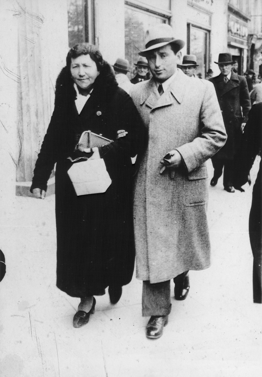 A young Jewish man walks with his mother along a commercial street in Lvov, Poland.  Pictured are Shmuel (Miles) Lerman and his mother Jochevet.