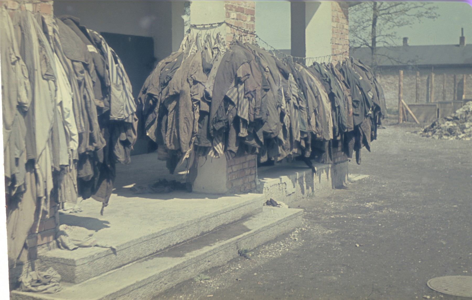 Prisoners' clothing and uniforms hang outside the crematorium in the newly liberated Dachau concentration camp.