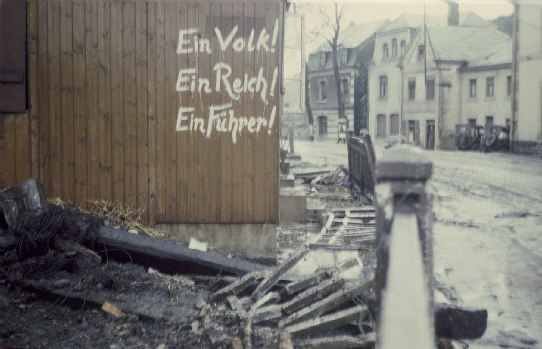 """German graffiti painted on the wall of a wooden building on a bomb-damaged street near the Dachau concentration camp.  The graffiti reads: """"One People! One Realm! One Leader!"""""""